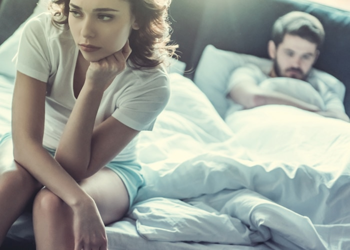 a sad woman sits on the bed, while a sad man staying down